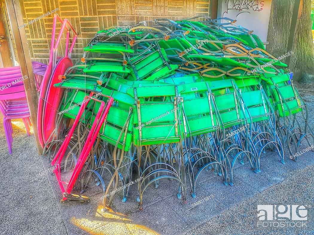 Stock Photo: Stack of green folding cafe outdoor terrace chairs outside cafe in winter, Sweden.