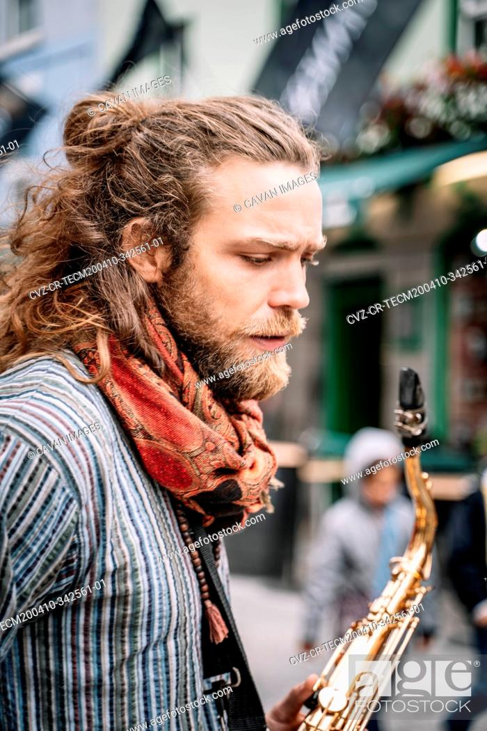Stock Photo: Vertical photo of man with long hair and beard dressed in hippie clothes with a saxophone.