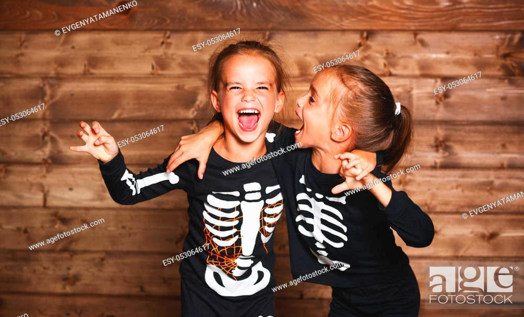 Stock Photo: holiday halloween. funny funny sisters twins children in carnival costumes skeleton on a wooden background.