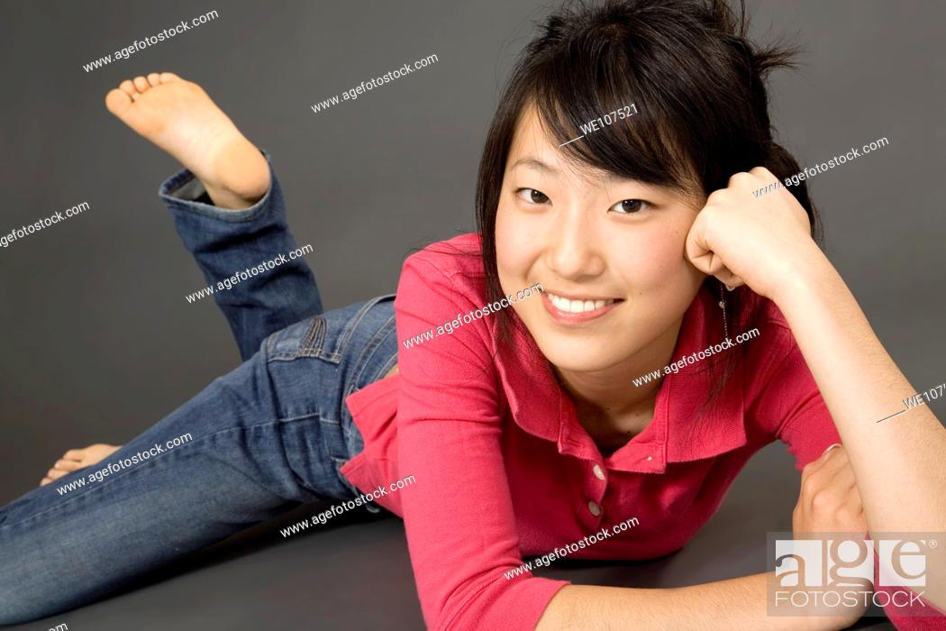Stock Photo: Asian Teenage girl posing on gray background with some attitude.