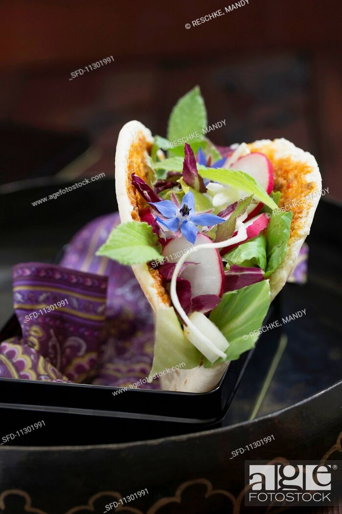 Stock Photo: A pita bread filled with a mixed leaf salad, radishes and borage flowers.