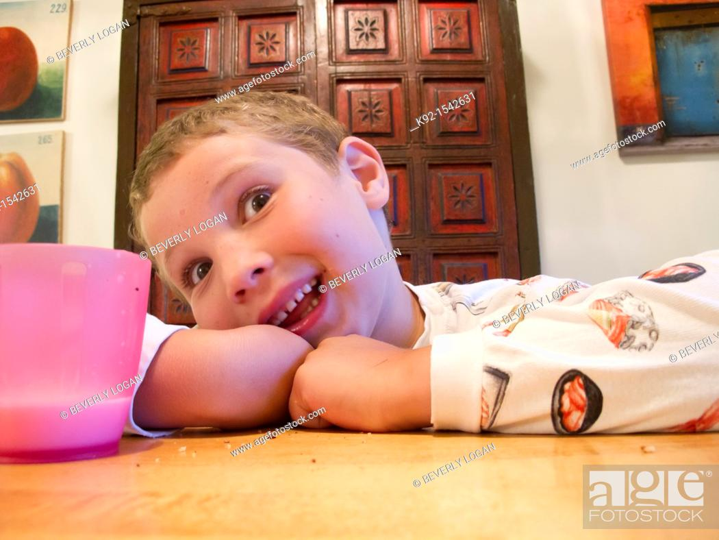 Stock Photo: Boy making a funny face while sitting at a table.
