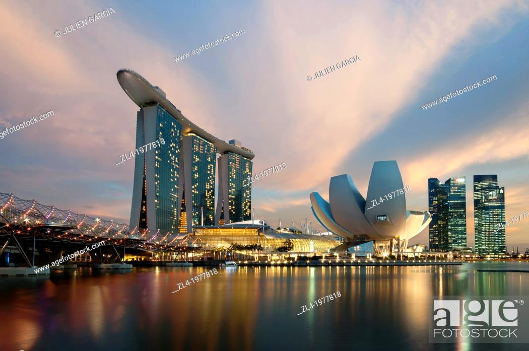 Stock Photo: Marina Bay Sands hotel at sunset with the ArtScience museum designed by the architect Moshe Safdie, the helix bridge on the left.