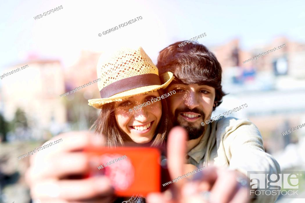 Stock Photo: Portrait of happy young couple taking selfie with smartphone.