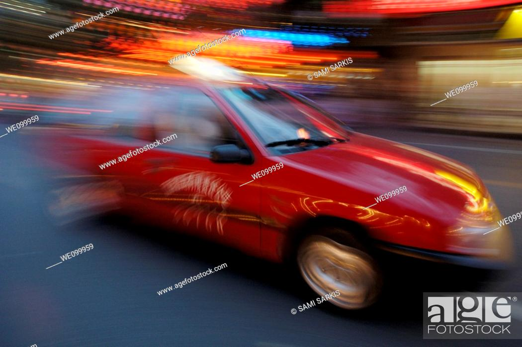 Stock Photo: Taxi passes by the Wangfujing markets with great speed at night in Beijing, China.