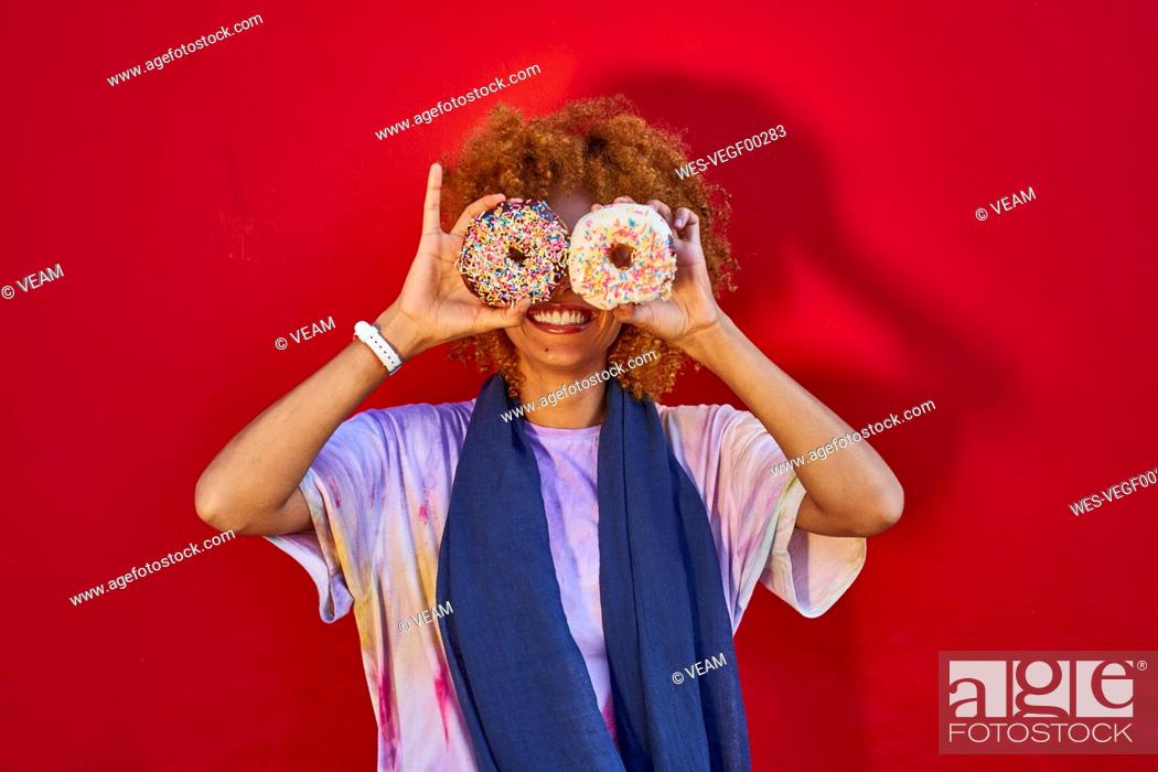 Stock Photo: Playful woman holding two donuts in front of her eyes.