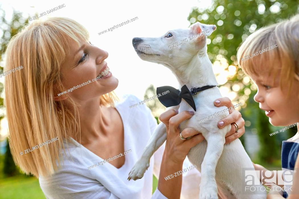 Stock Photo: Happy woman with daughter holding dog wearing a bowtie outdoors.