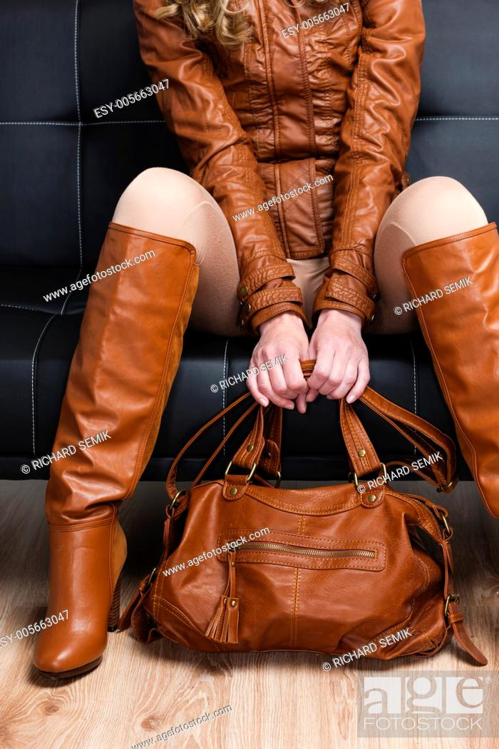 Stock Photo: detail of sitting woman in brown clothes holding a handbag.