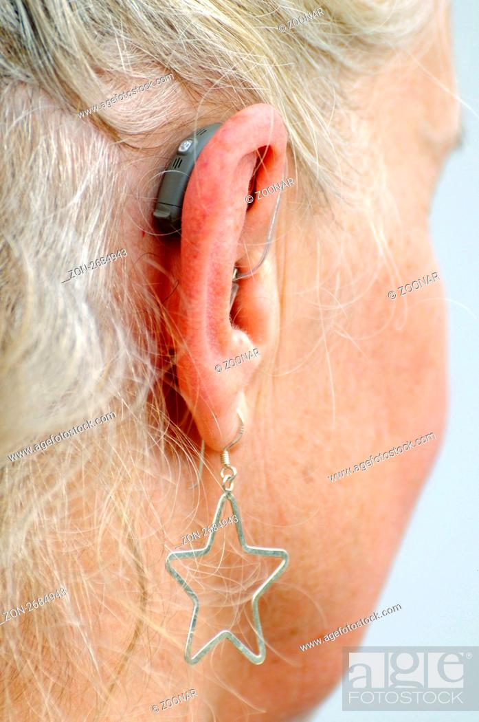 Stock Photo Modern Small Hearing Aid Behind The Ear Of A Woman 55 60 Years Earring Hardness Modernes Kleines Geraet Am Ohr Einer