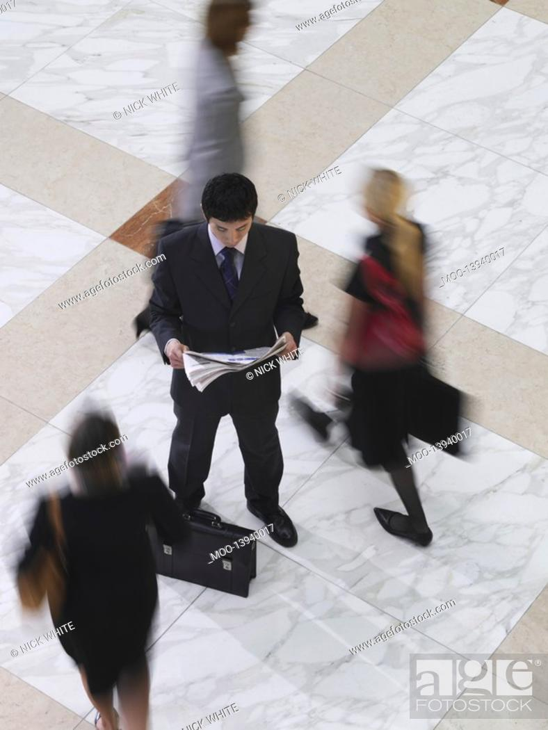 Stock Photo: Business man reading newspaper amongst people walking elevated view long exposure.