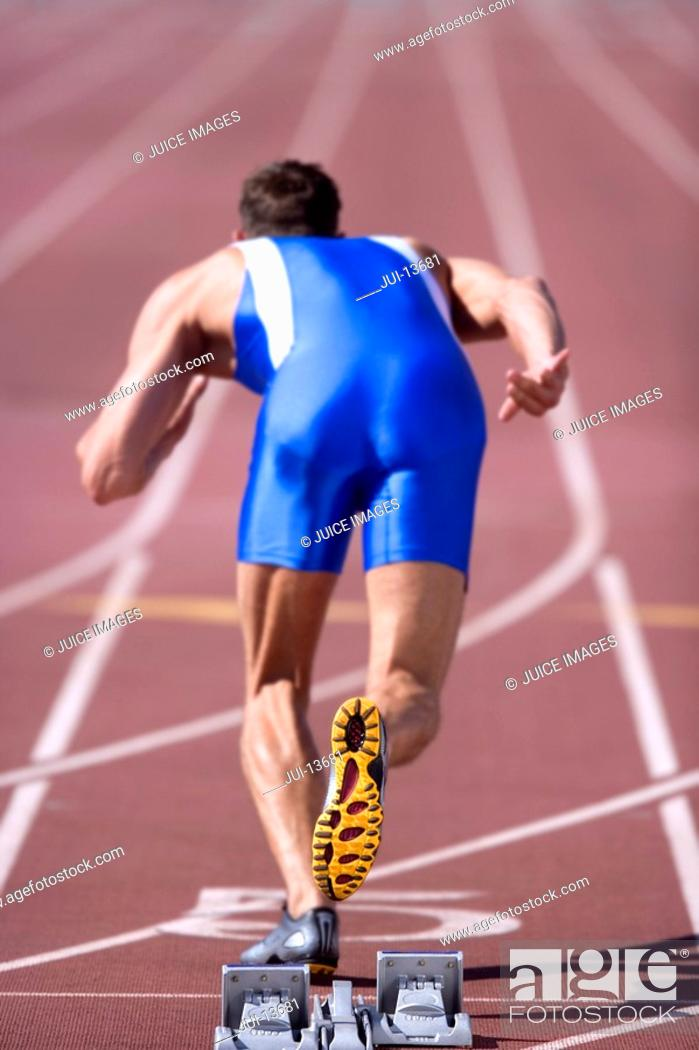 Stock Photo: Male athlete by starting blocks, rear view.