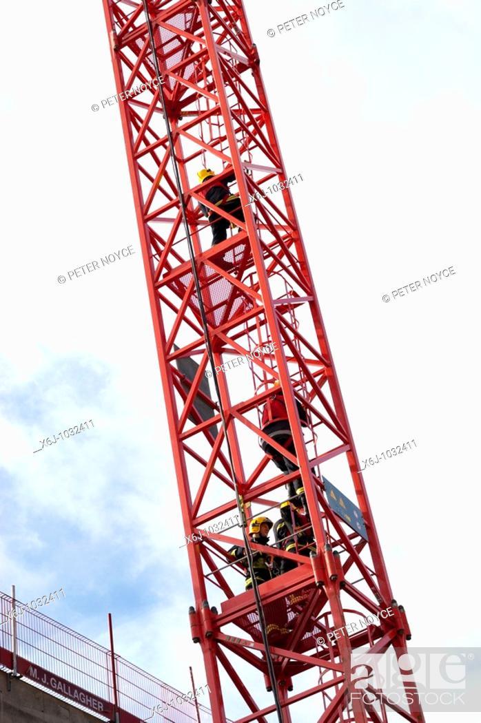 Stock Photo: firemen climbing a tower crane.