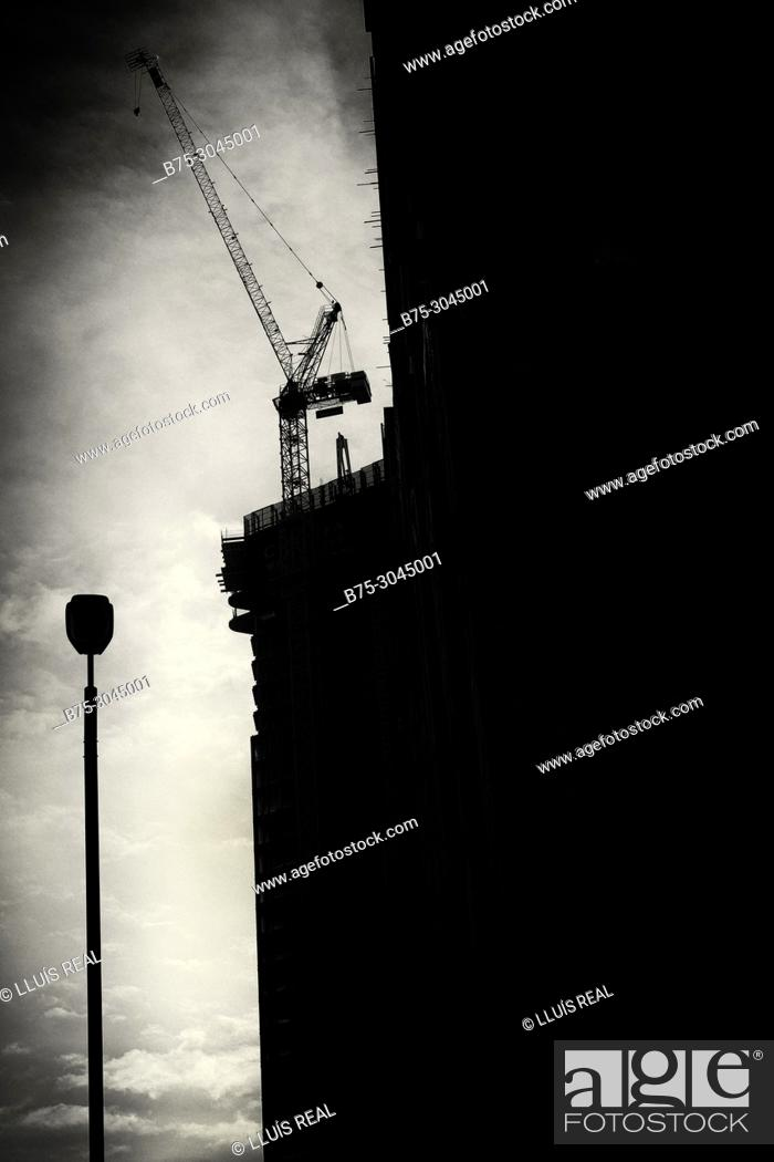 Stock Photo: Silhouette of a building in rehabilitation with crane and lamppost, clouds in the sky. Lots Rd. Chelsea, London, England.