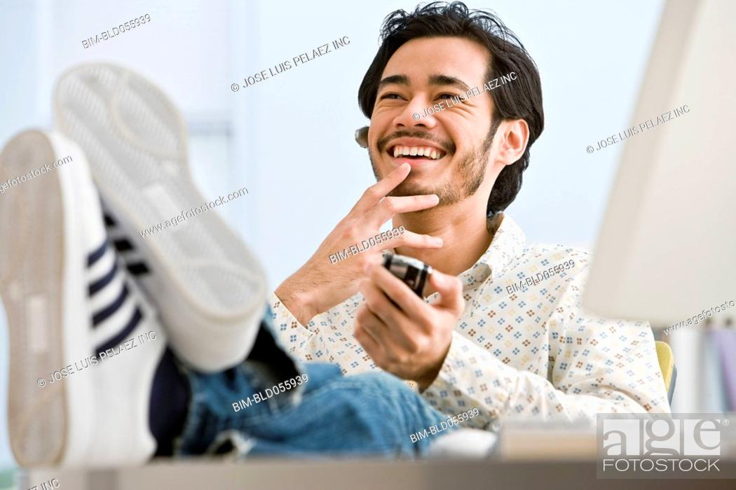 Stock Photo: Asian businessman holding cell phone.