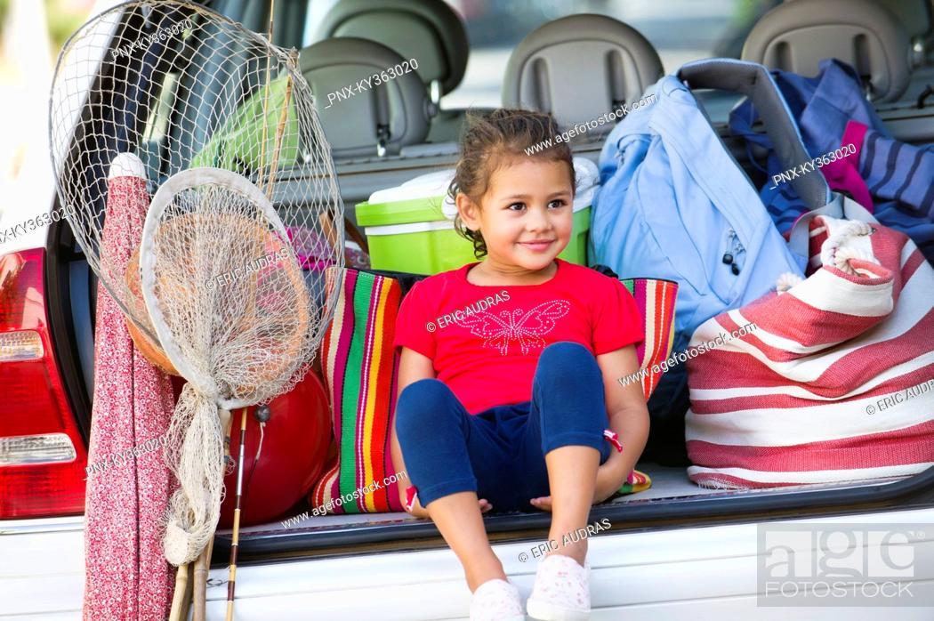 Stock Photo: Cute little girl sitting in car trunk.