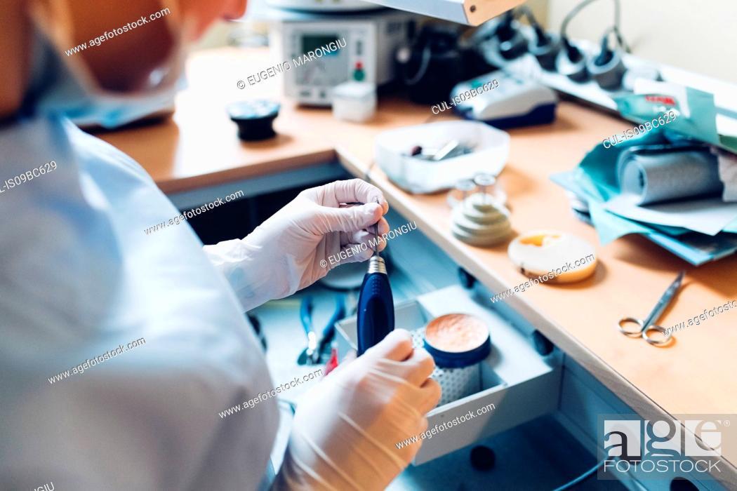 Stock Photo: Female dentist handling dentistry equipment in dentist office, mid section.