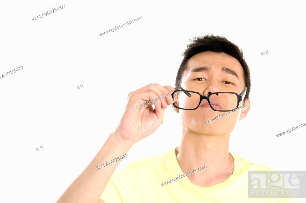 Stock Photo: Male university student holding eyeglasses.