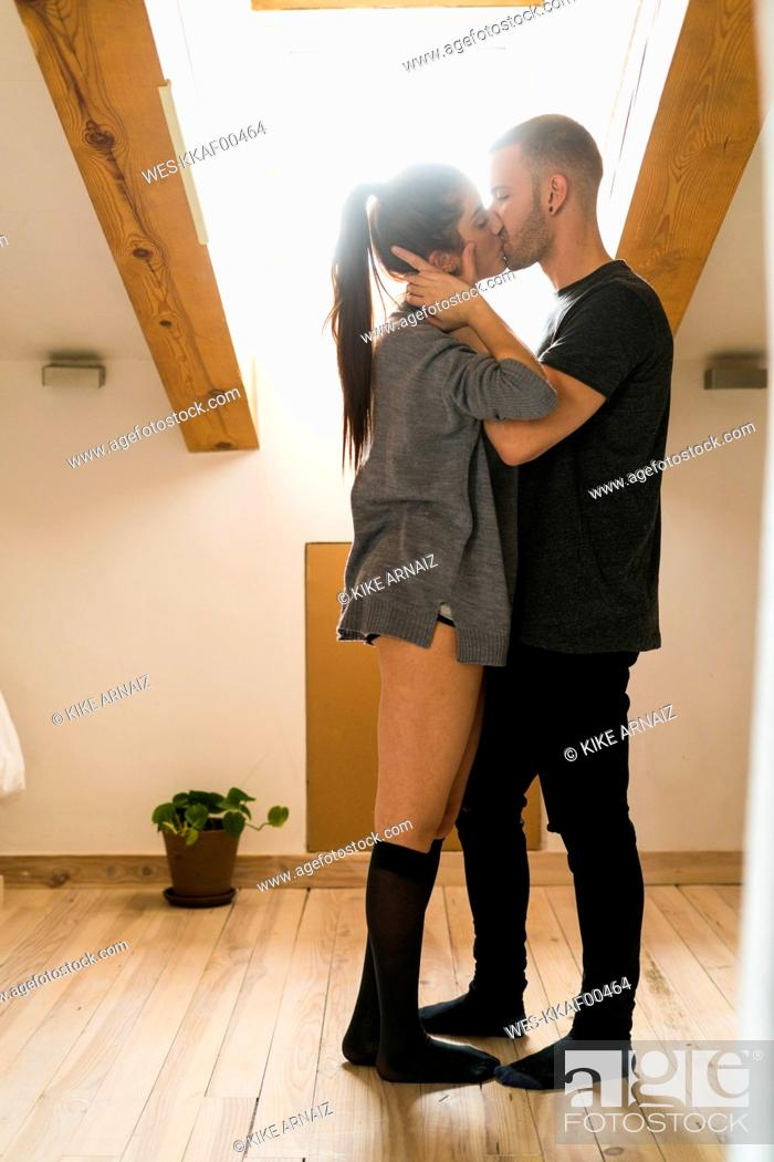 Stock Photo: Amorous couple standing at home, kissing and ambracing passionately.