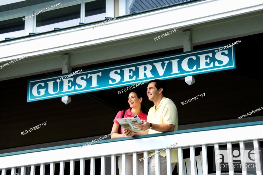 Stock Photo: Couple looking out at guest services.