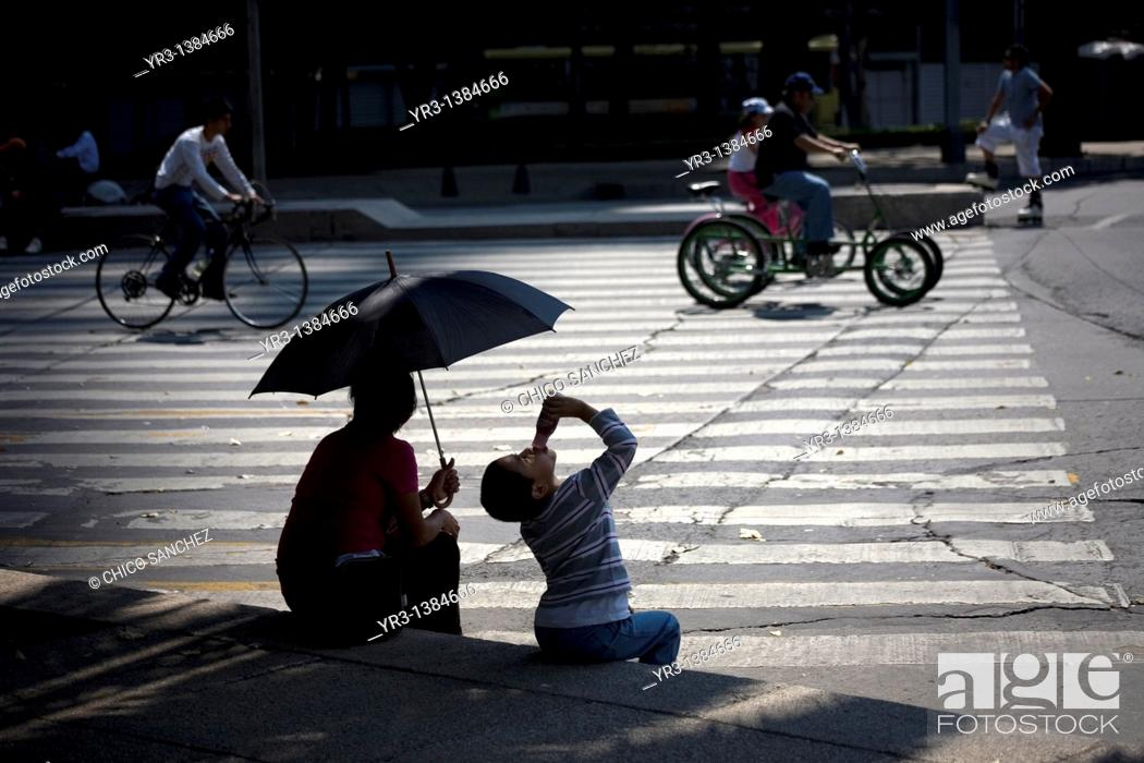 Stock Photo: A boy drinks yogurt next to his mother holding an umbrella to shade them from the sun as they watch cyclists ride along Paseo de la Reforma Avenue in Mexico.