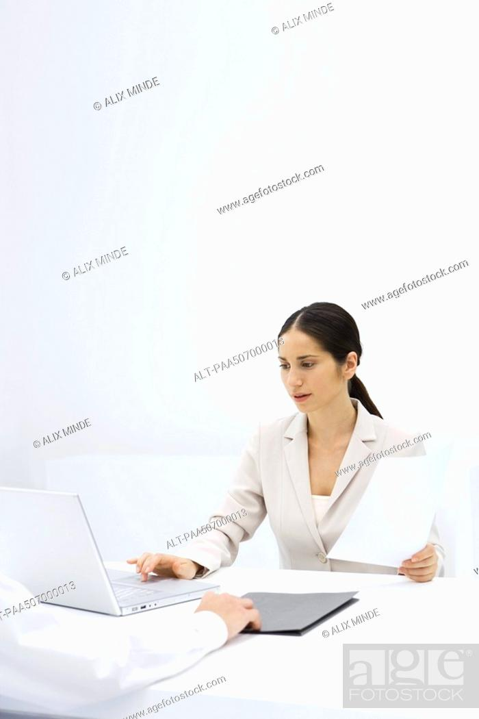 Stock Photo: Woman using laptop while holding a document, cropped view of arm pushing folder across desk.