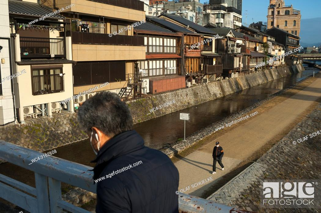 Stock Photo: 26. 12. 2017, Kyoto, Japan, Asia - A man is seen crossing a bridge over the Kamo River in Kyoto at dawn.