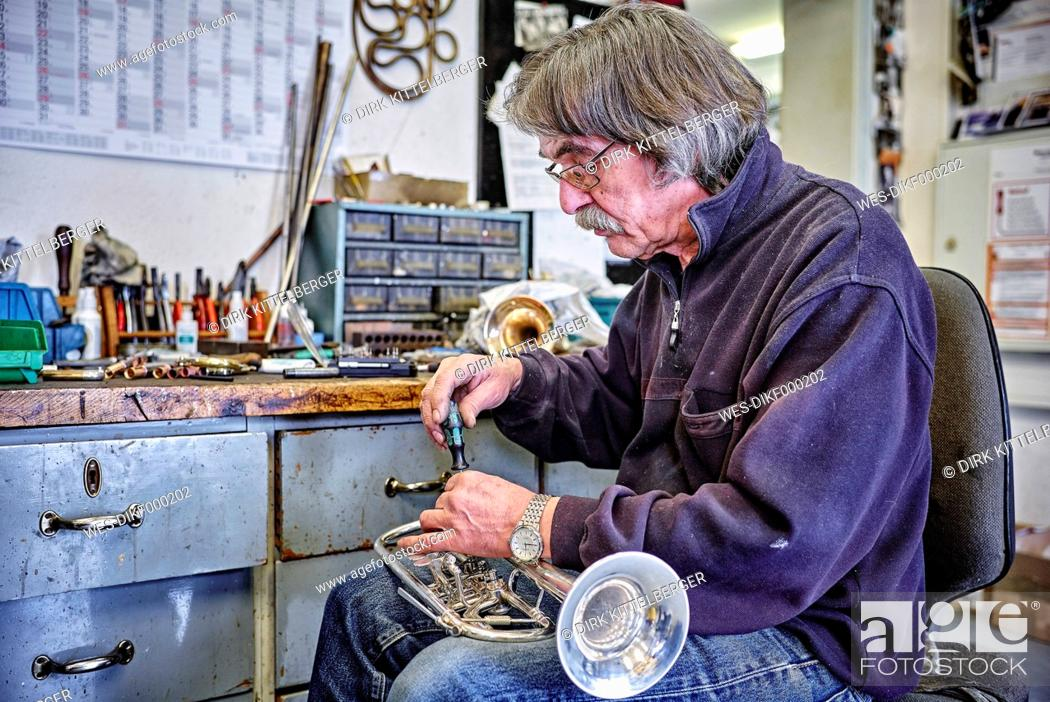 Stock Photo: Instrument maker repairing trumpet in workshop.