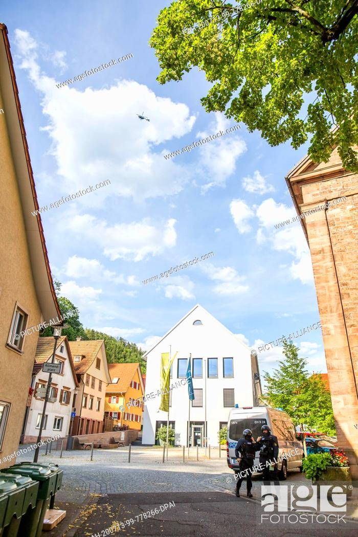 Stock Photo: 13 July 2020, Baden-Wuerttemberg, Oppenau: Two police officers are standing near the centre of Oppenau, while a police helicopter circles above them.