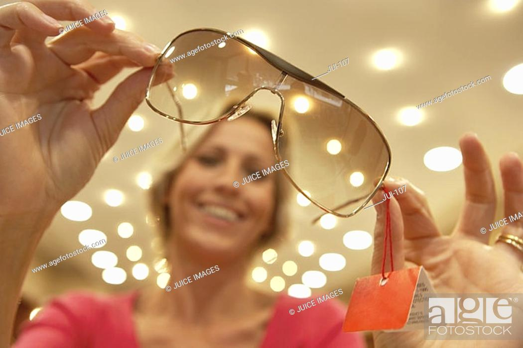 Stock Photo: Woman holding pair of sunglasses in shop, portrait, focus on foreground, low angle view tilt.