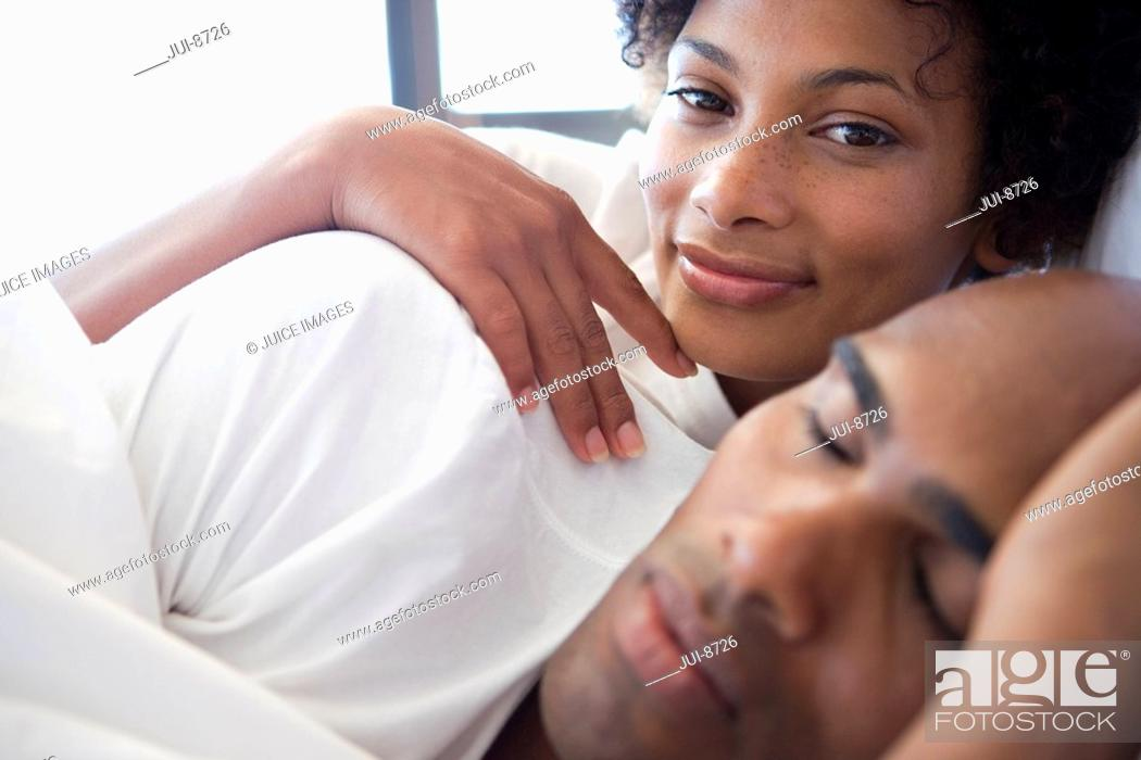 Stock Photo: Young couple lying in bed, woman smiling in background, close-up.