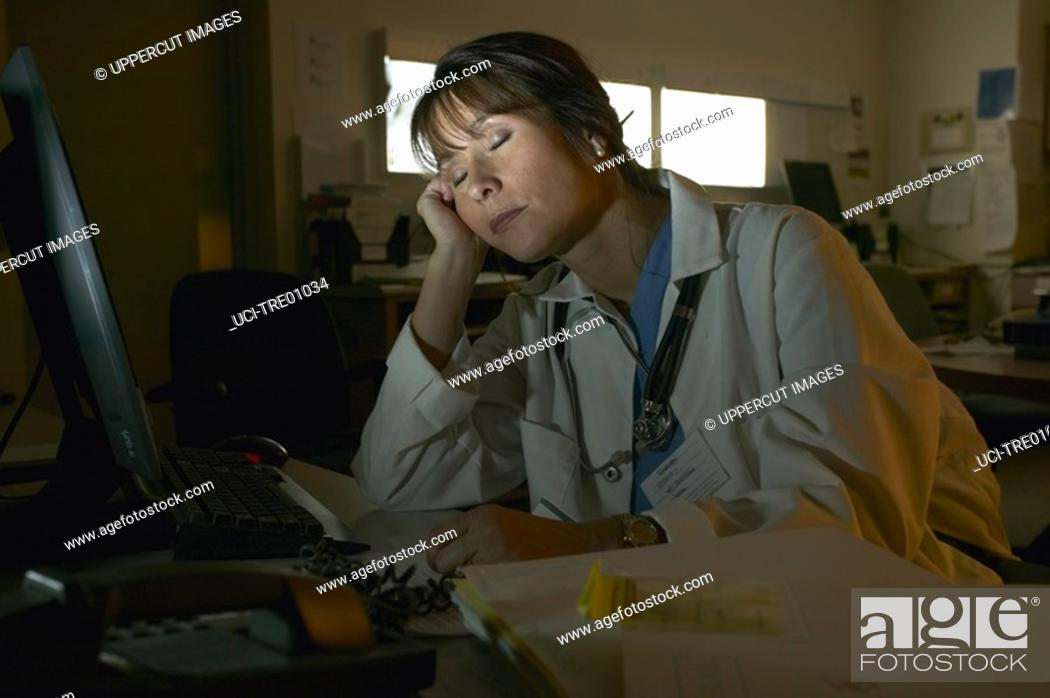 Stock Photo: Doctor asleep at desk.