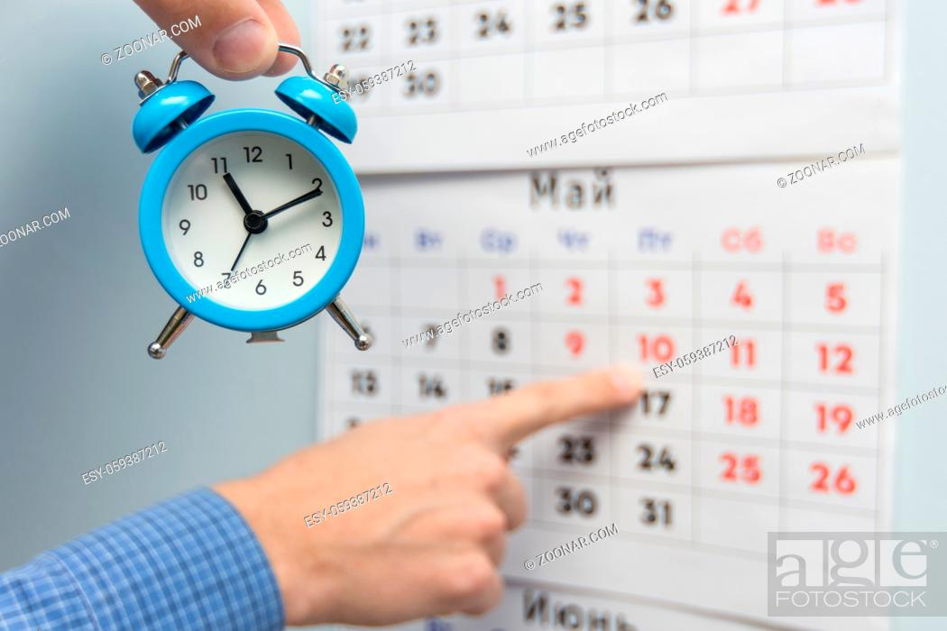 Imagen: A hand holds a small alarm clock, in the background a hand points to long weekends and holidays on a wall calendar.