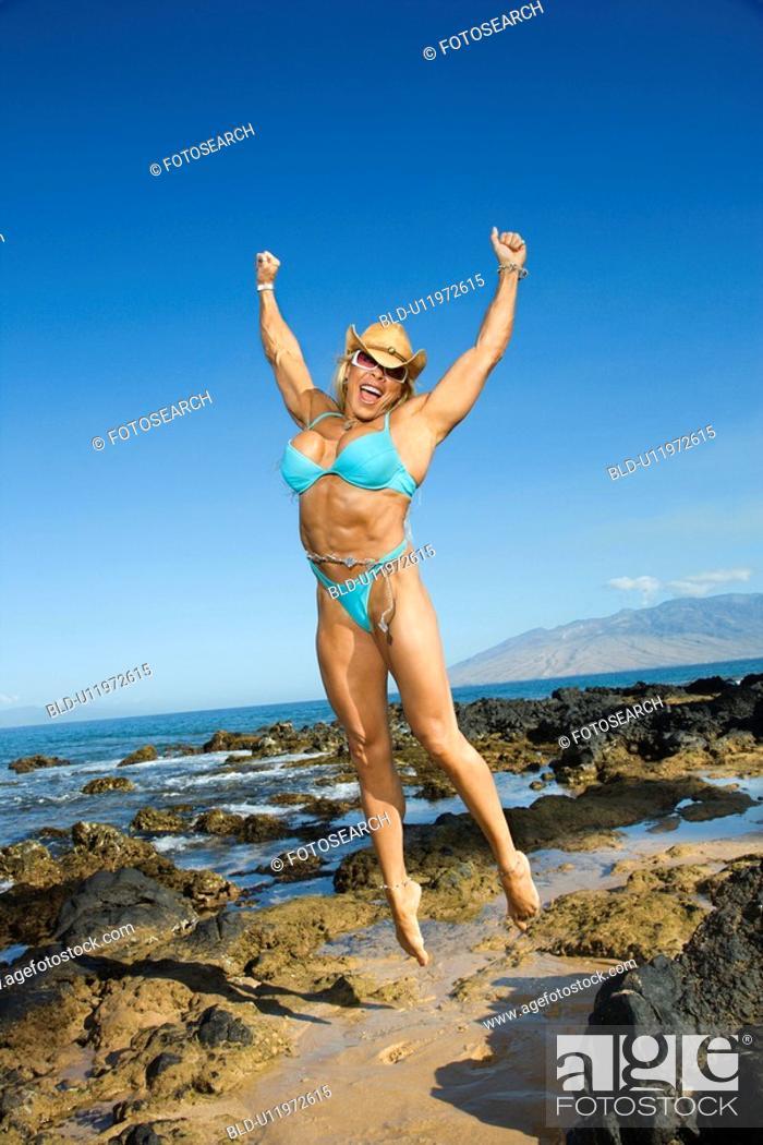 Stock Photo: Pretty Caucasian mid adult woman bodybuilder in bikini jumping in air on beach.