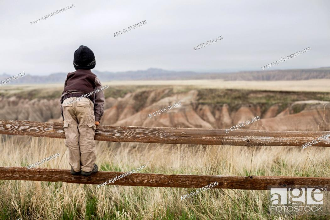 Stock Photo: A 4 year old Japanese American boy dressed as an explorer with a hat and vest shoots surveys the land while standing on the rail of a wooden fence in as he.