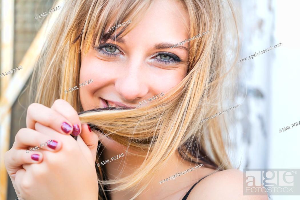 Stock Photo: Teen girl headshot close-up shy behind messy hair.