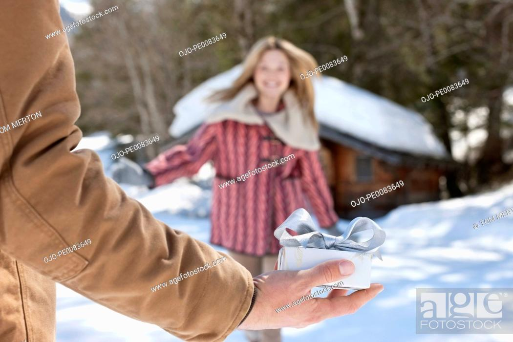 Stock Photo: Woman running toward man holding Christmas gift in snow.