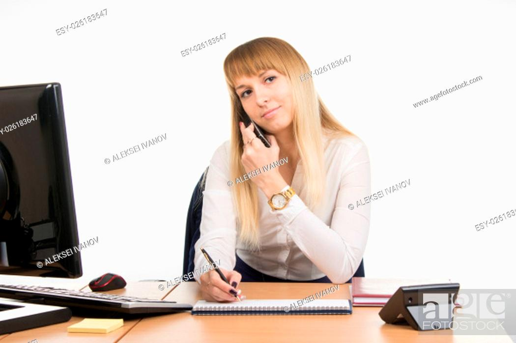 Stock Photo: young beautiful business woman sitting at office desk working, isolated on white background.