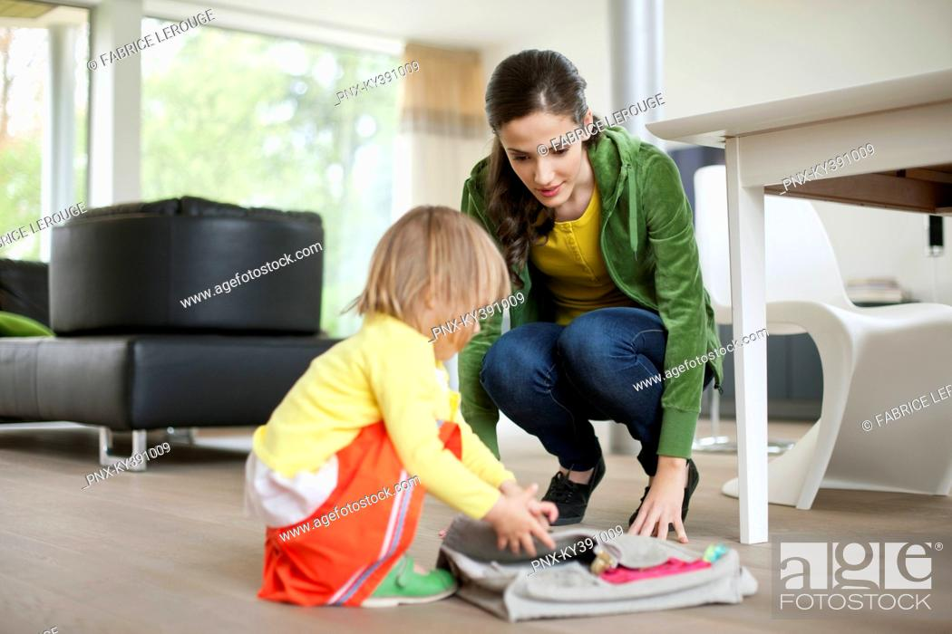 Stock Photo: Woman helping her daughter to get ready for school.