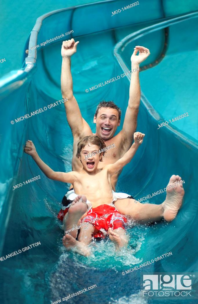 Stock Photo: Father and son 7-9 with arms outstretched on water slide.