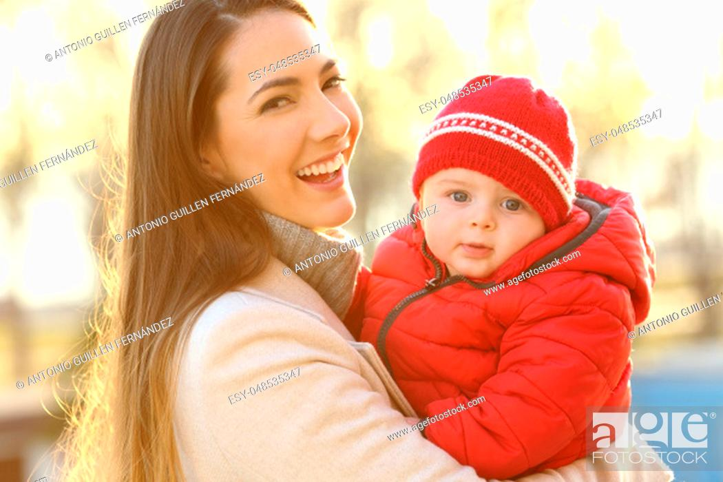Stock Photo: Portrait of a smiley mother posing with her baby keeping warm wearing a red jacket outdoors in winter.