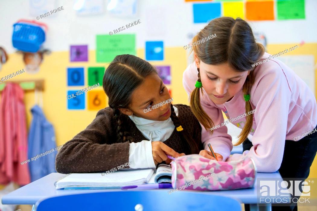 Stock Photo: Primary schoolgirl helping friend with workbook in classroom.