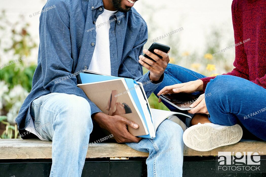 Stock Photo: Students sitting together and using smart phone.
