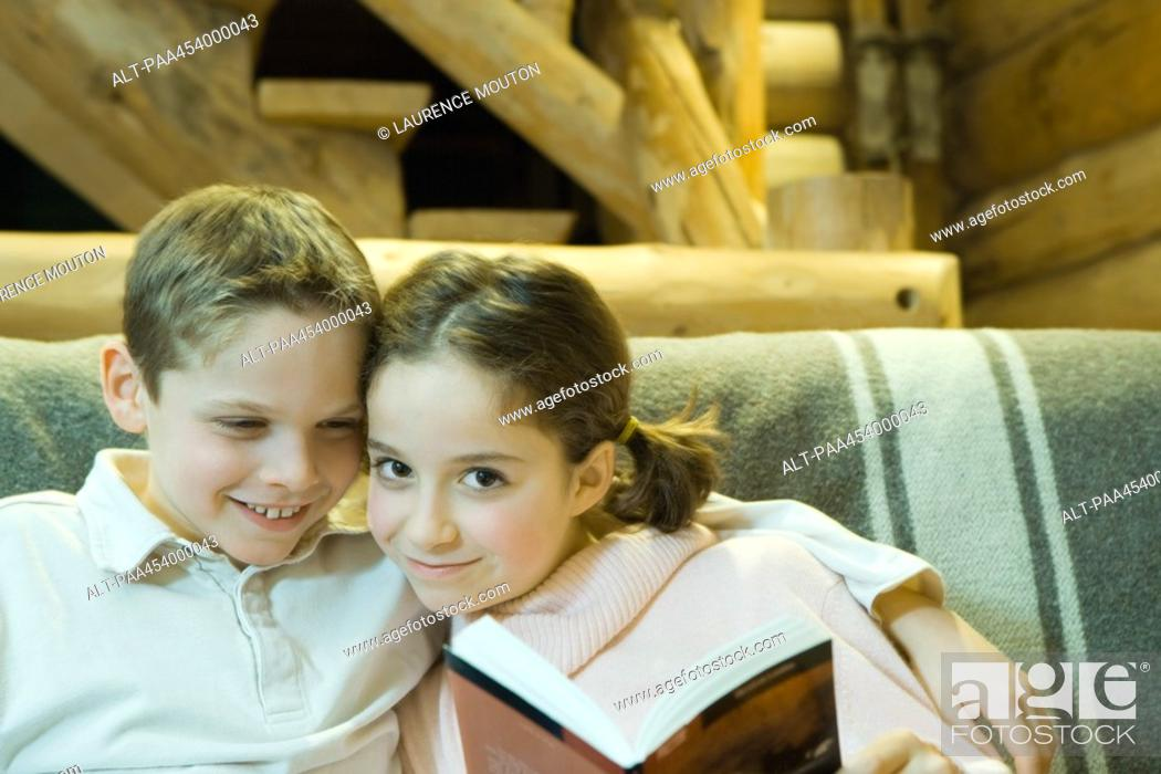 Stock Photo: Boy and girl reading together, smiling at camera, cheek to cheek.