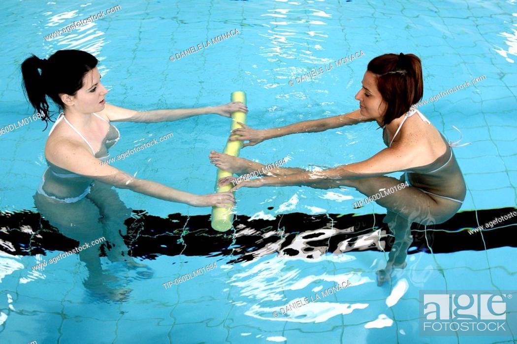 Stock Photo: Women in swimming pool doing pilates exercise.