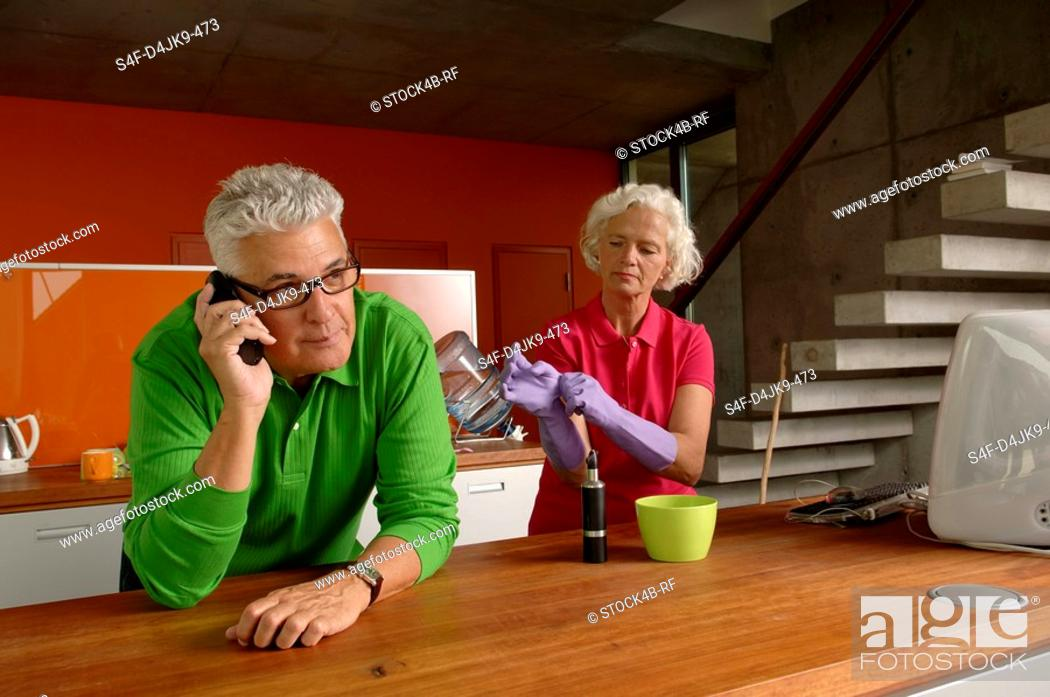Stock Photo: Senior man on the phone while his wife is putting on rubber gloves.