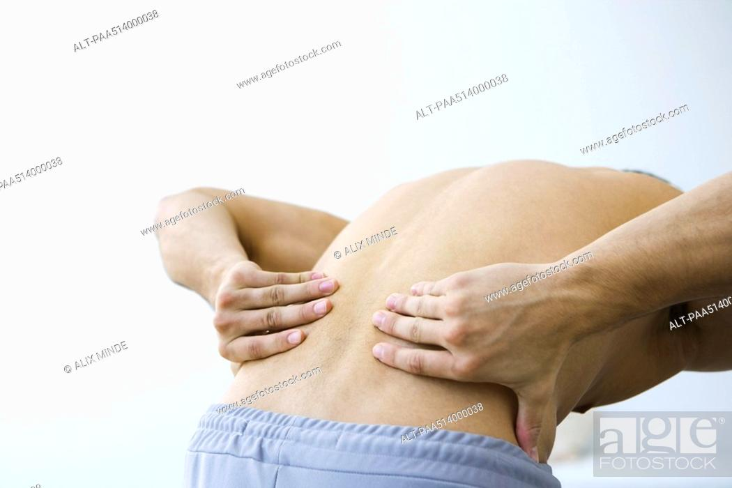 Stock Photo: Man bending over, holding lower back, cropped view.