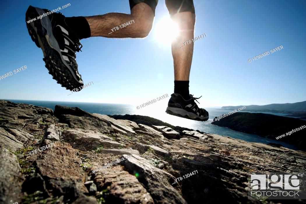 Stock Photo: Man running along a rocky coastal path.
