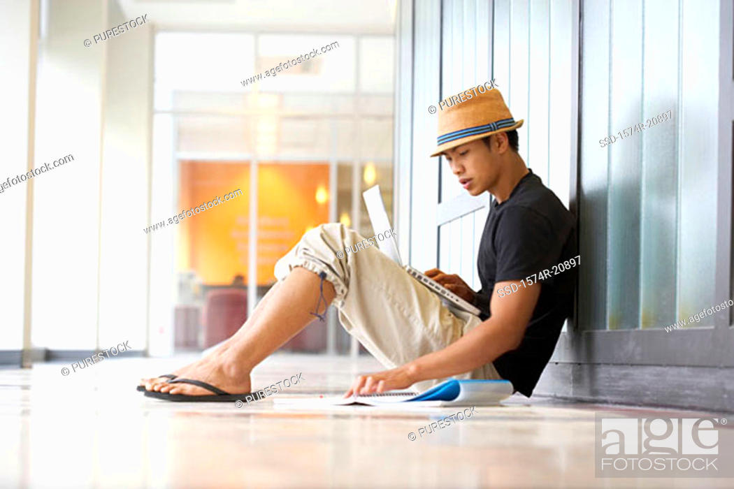Stock Photo: Side profile of a college student sitting in a corridor and reading a book.