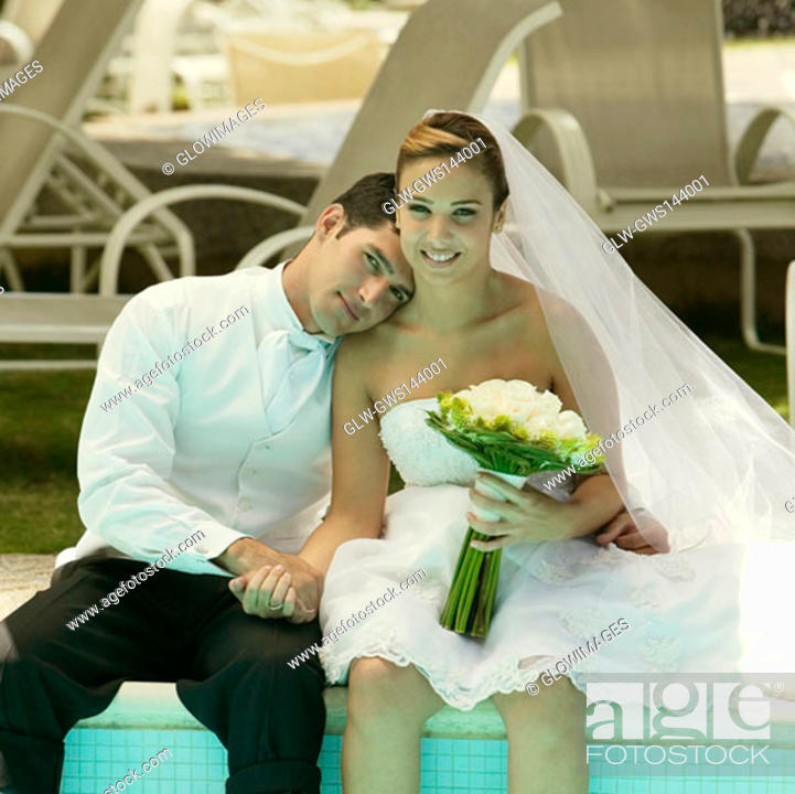 Stock Photo: Portrait of a newlywed couple sitting at the poolside.