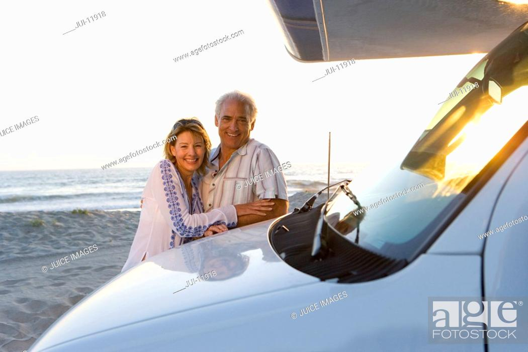 Stock Photo: Mature couple embracing by motor home on beach, smiling, portrait, dusk.